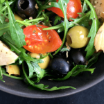 Italian Arugula Salad is the perfect vegan side dish to any meal. Full of tasty Mediterranean ingredients like olives, artichokes, basil and oregano. Make it for a simple lunch, BBQ or a fancy dinner party. | The Green Loot #vegan