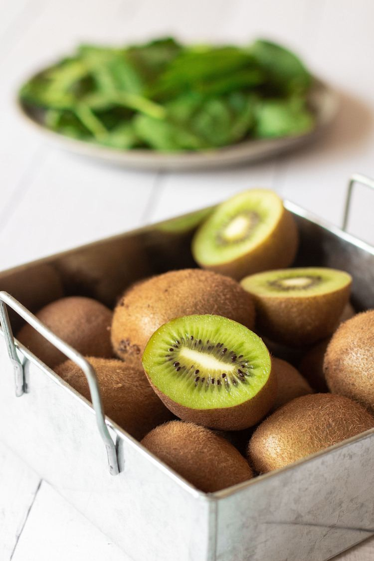 kiwis in a silver basket, spinach leaves in the background