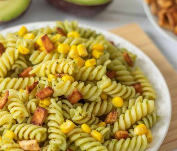 Vegan Avocado Pasta with Tofu Bacon on a table