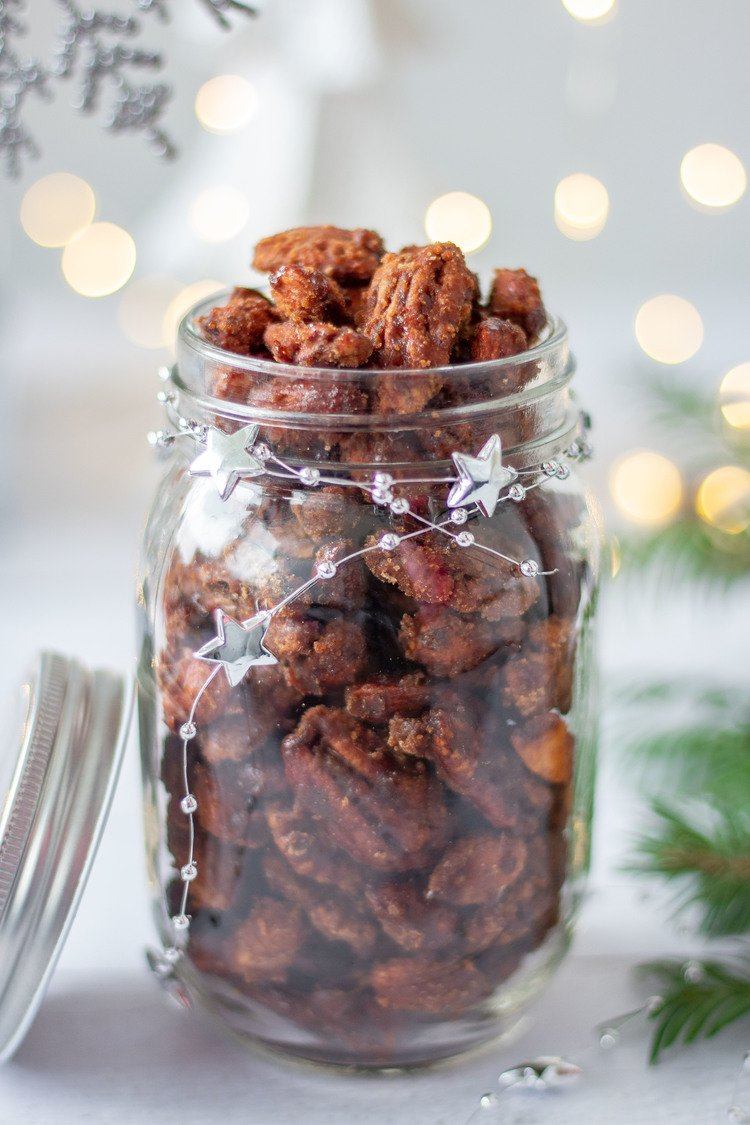 Gingerbread Candied Nuts in a jar in front of Christmas lights