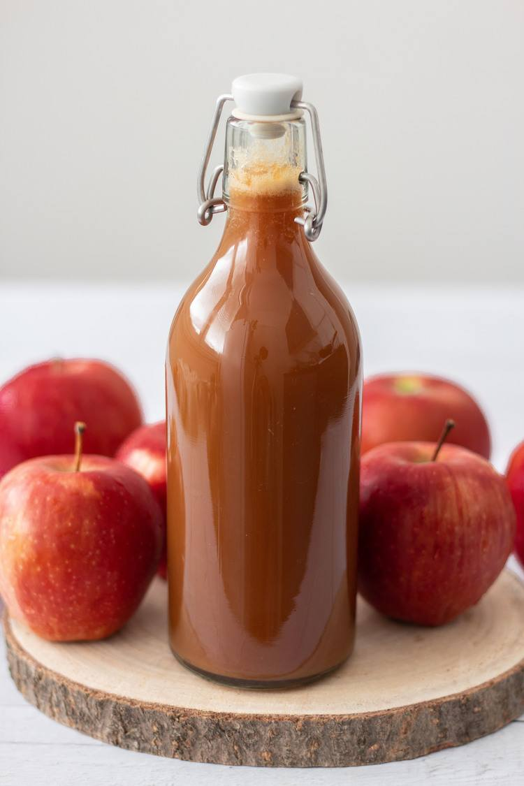 Homemade Apple Juice in a glass bottle with fresh apples